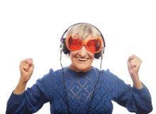 Musique de écoute drôle de vieille dame et de représentation pouces  Photo libre de droits