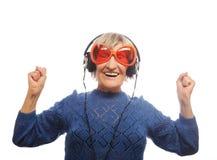 Musique de écoute drôle de vieille dame et de représentation pouces  Images stock
