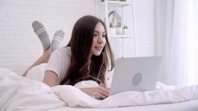 Musique de écoute femelle heureuse avec des écouteurs et de recherche dans un ordinateur portable chansons à la maison Concept de clips vidéos