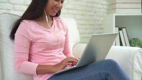 Musique de écoute femelle heureuse avec des écouteurs et de recherche dans un ordinateur portable chansons à la maison Concept de banque de vidéos