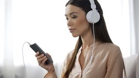Musique de écoute de femme asiatique dans des écouteurs, station de radio aimante, plaisir image stock