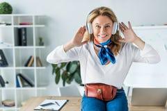 musique de écoute de femme d'affaires heureuse attirante dans des écouteurs images stock