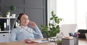Musique de écoute de femme d'affaires utilisant l'ordinateur portable et les écouteurs au bureau banque de vidéos