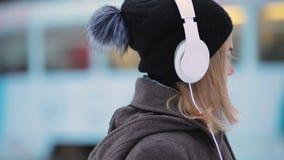 Musique de écoute de femme dans des écouteurs à la ville de soirée d'hiver banque de vidéos