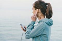 Musique de écoute de femme de forme physique dans des écouteurs Images stock