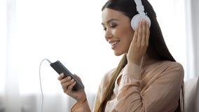 Musique de écoute de femme mignonne dans des écouteurs, station de radio aimante, plaisir photographie stock