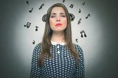 Musique de écoute de femme par l'intermédiaire des écouteurs Photo stock