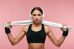 Musique de écoute de femme de sport dans des écouteurs sur la formation photo libre de droits