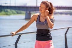 Musique de écoute de femme sportive avant le fonctionnement Liste d'athlète féminin Photo stock