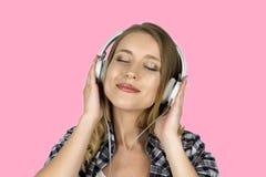Musique de écoute de fille à l'arrière-plan rose d'isolement par écouteurs photos libres de droits