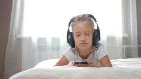 Musique de écoute de fille Fermez-vous vers le haut de l'écolière de portrait 7-8 ans utilisant le téléphone portable dans les éc clips vidéos