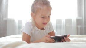 Musique de écoute de fille Fermez-vous vers le haut de l'écolière de portrait 7-8 ans utilisant le téléphone portable dans les éc banque de vidéos