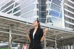 Musique de écoute de jeune femme asiatique décontractée avec le téléphone intelligent mobile dans la ville urbaine images libres de droits