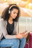Musique de écoute de jeune femme de couleur heureuse avec des écouteurs et le mobi Images stock
