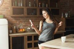 Musique de écoute de jeune femme heureuse dans la cuisine photographie stock