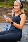Musique de écoute de jeune femme sportive avec des écouteurs et Smartphon photo stock