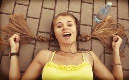 Musique de écoute de jeune fille attirante heureuse avec l'écouteur Photos libres de droits