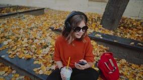 Musique de écoute mignonne de jeune fille dans des écouteurs, style urbain, années de l'adolescence élégantes de hippie se reposa banque de vidéos
