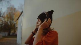 Musique de écoute mignonne de jeune fille dans les écouteurs et la danse, style urbain, années de l'adolescence élégantes de hipp clips vidéos