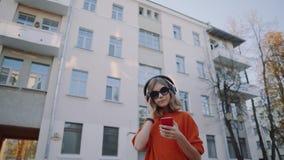 Musique de écoute mignonne de jeune fille dans les écouteurs, le style urbain, années de l'adolescence élégantes de hippie choisi clips vidéos