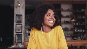 Musique de écoute de sourire de jeune femme sur l'écouteur en café clips vidéos