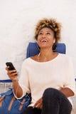 Musique de écoute de sourire de voyageuse de jeune femme avec l'écouteur dehors Photographie stock libre de droits