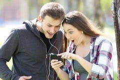 Musique de écoute stupéfaite de couples sur la ligne Photos stock