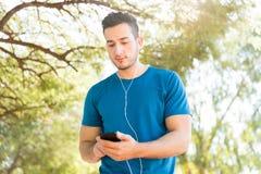 Musique de écoute de taqueur avec les écouteurs et le téléphone portable en parc image stock