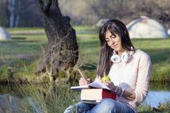 Musique de étude et de écoute de jeune femme en parc d'automne Images libres de droits