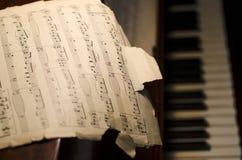 Musique de feuille déchirée en lambeaux sur le piano Photo libre de droits