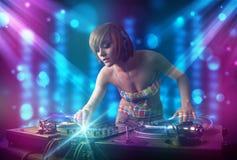Musique de mélange de fille du DJ dans un club avec les lumières bleues et pourpres Image stock