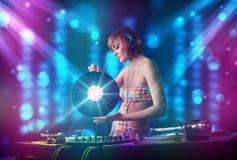 Musique de mélange de fille du DJ dans un club avec les lumières bleues et pourpres Photographie stock