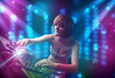 Musique de mélange de fille du DJ dans un club avec les lumières bleues et pourpres Photo stock