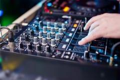 Musique de mélange du DJ sur la console à la boîte de nuit Photo stock