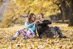 Musique de repos et de écoute de beaux jeunes couples après la formation réussie en parc Coeur de forme de main Photographie stock libre de droits