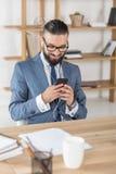 Musique et à l'aide de écoute de sourire d'homme d'affaires du smartphone dans des écouteurs sur le lieu de travail Images libres de droits