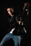 Musique et créativité Jeune homme beau dans un T-shirt, une veste et des jeans, avec une guitare électrique, sur un fond d'isolem Photo stock