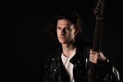 Musique et créativité Jeune homme beau dans un T-shirt, une veste et des jeans, avec une guitare électrique, sur un fond d'isolem Photo libre de droits