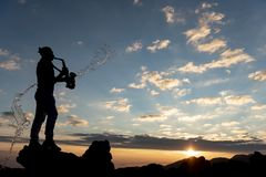 Musique et lever de soleil ; un beau lever de soleil et un saxophoniste énergique photographie stock libre de droits