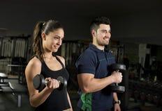 Muskel för kvinnautbildningsbiceps i idrottshall arkivfoto