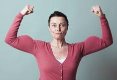 Muskel och kvinnligsjälvständighetmetafor för rolig 40-talkvinna Royaltyfri Fotografi