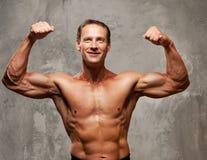 Muskel-Sportler auf einem grauen Hintergrund Lizenzfreies Stockbild