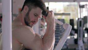 Muskelbyggnad, ung sportman som gör styrkaövningar på muskler av armar på simulatorn under maktgenomkörare i idrottshall stock video