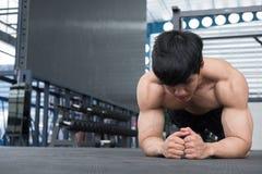 Muskelman som gör plankaposition i idrottshall kroppsbyggaremanarbete royaltyfri bild