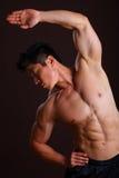 Muskelman som sträcker den vänster armen och abs Fotografering för Bildbyråer