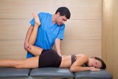 Muskeln driver terapi på kvinna lägger benen på ryggen knäet Arkivfoto