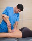 Muskeln driver terapi på kvinna lägger benen på ryggen knäet Arkivbild
