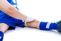 muskeln för closeupskadabenet smärtar för sportfläck för löpare running trycka på för lår Doktorsförsta hjälpen på låret av fotbo Arkivfoto
