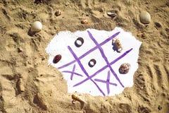 Muskelryckning Tac Toe och vigselringar på stranden Gifta sig i vändkretsbegreppet Arkivbild