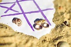 Muskelryckning Tac Toe och vigselringar på stranden Gifta sig i vändkretsbegreppet Royaltyfri Bild